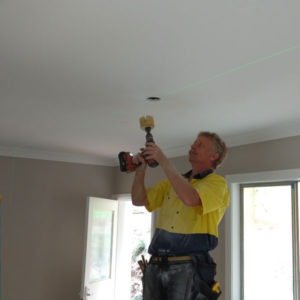 A photo of our electrician installing downlights